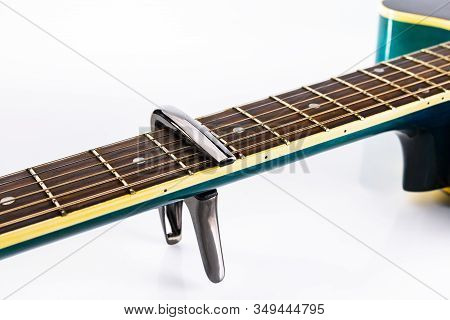 A Capotasto On A Fretboard Of Acoustic Guitar, On A White Background, Close-up, Side View.