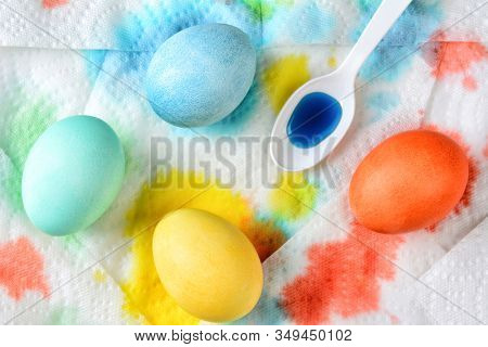 Flat lay Easter Eggs drying on paper towels. The towels are stained with excess dye. Horizontal format.