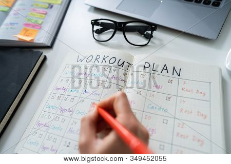 Close-up Of A Human Hand Making Workout Plan On Notebook