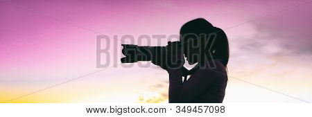 Professional photographer woman silhouette taking night photo during photography safari travel tour for tourists. Girl holding slr camera with telelens panoramic banner.
