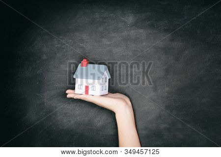 Real Estate blackboard background - New home ownership woman showing miniature house toy for homeowner concept billboard.