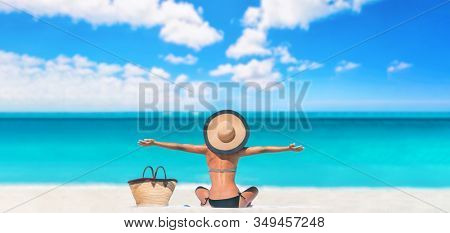 Beach caribbean travel vacation woman happy carefree with open arms on summer holiday panoramic banner. Tourist sun sunbathing bikini body skincare sun protection with hat enjoying summer holidays.