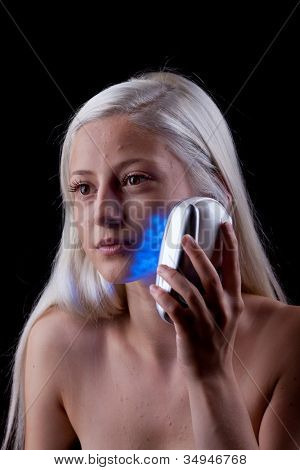 Young woman with skin problems getting photo-therapy by blue light