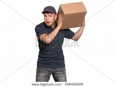 Portrait of Delivery man in cap holding cardboard box near his ear and listening something. Handsome funny man Courier, isolated on white background.