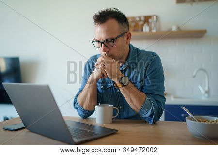Thoughtful Serious Young Man Lost In Thoughts In Front Of Laptop, Focused Businessman Thinking Of Pr