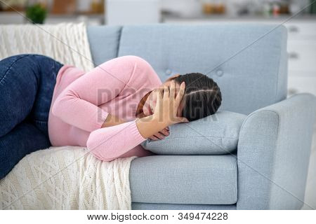 Full-figured Young Woman In A Pink Shirt Lying On A Sofa