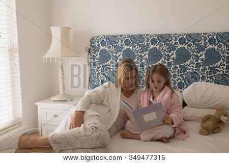 Front view of caring mother with her daughter reading storybook in bedroom at home