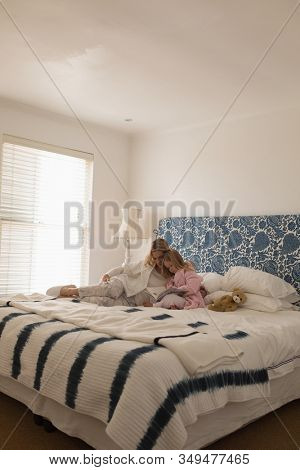 Distant side view of loving mother with her young daughter reading storybook in bedroom at home