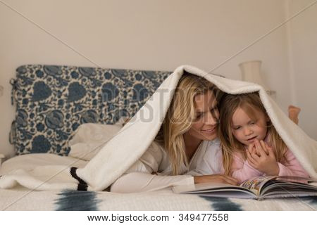 Front view of happy mother spending time with her daughter by reading storybook under blanket in bedroom at home