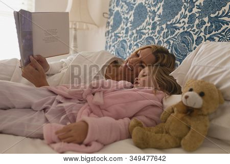 Side view of happy mother with her young daughter reading storybook in bedroom at home
