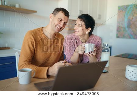 Beautiful Young Married Couple Having Breakfast Together Working On Laptop At Table Or Reading News.