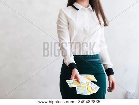 Mysticism In Everyday Life. Esoteric In Tarot Cards. A Girl In A Business Suit Divines On Tarot Card
