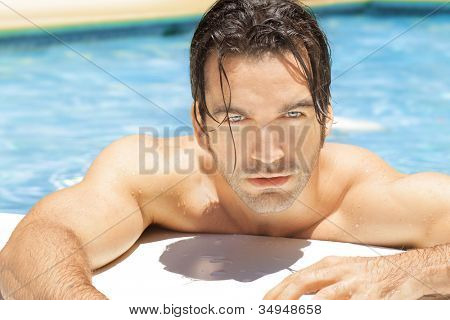 Sexy young man in bright blue swimming pool relaxing