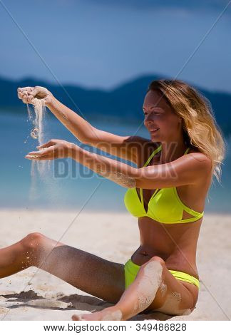 Beautiful Slender Blonde Girl In A Yellow Bikini Swimsuit Sits On A Sea Beach And Spills White Sand