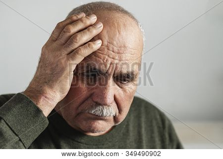 Forgetful Senior Man Holding A Hand To His Head