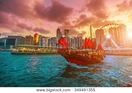 Sunset Red-sail Junk Boat With Skyscrapers And Building Of Hong Kong City Skyline In China.