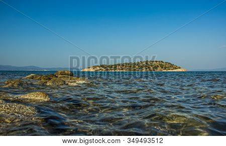 Mediterranean Sea Side Water Lagoon Scenic Landscape View Of Island And Rocky Shore Line Foreground