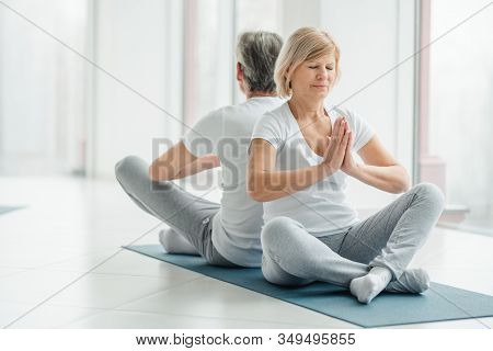 Yoga Helps Our Health. Morning Meditation. Sport Concept.senior Couple In The White Gym Studio.
