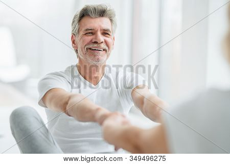 Sports And Healthy Lifestyle.handsome Mature Man Holding Hand His Wife When Doing Stretching In The