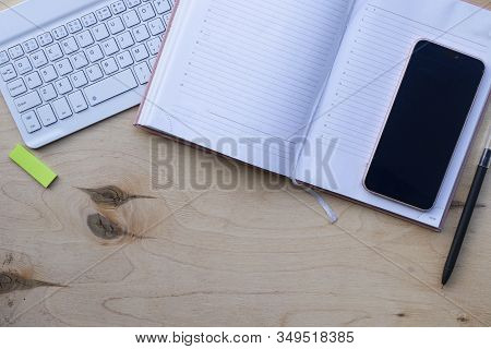 Wooden Desktop With Keyboard, Diary And Pen, Glasses For The Computer. Working Environment, Receivin