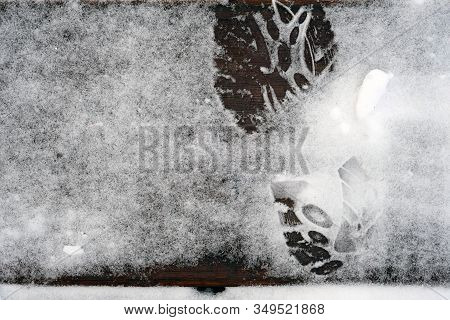 Imprint Of Shoes On Steps Covered With Snow. Snow And Imprint From The Sole. Ice In The Winter Dange