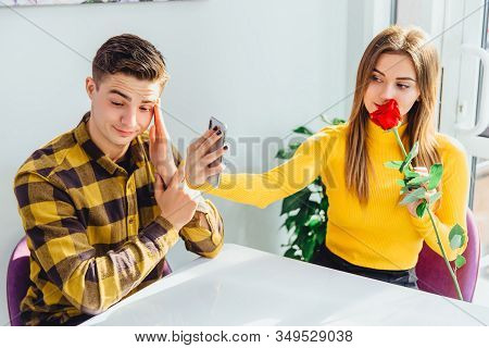 Annoyed Boy Waiting, Looking Disapprovingly, While His Dirlfriend Is Making Selfie With Red Rose He