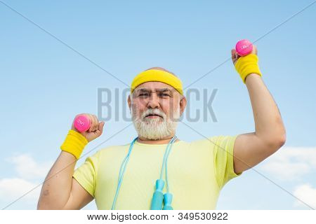 Happy Senior Man With Dumbbell Looking At Camera. Health Club Or Rehabilitation Center For Elderly A