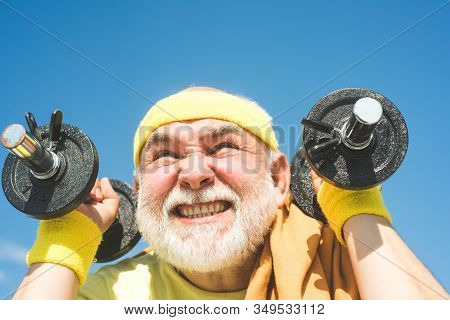Age Is No Excuse To Slack On Your Health. Senior Man Exercising On Blue Sky. Health Club Or Rehabili