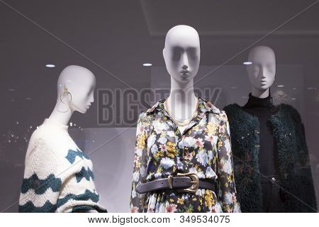 Three Or A Group Of Female Bald White Mannequins In A Shop Window. Mannequins Are Dressed In Dresses