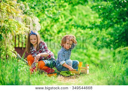 Cute Little Children Enjoying On Farm. Children Farmer Concept. Children Play In Spring Garden. Happ