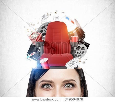 Close Up Of Astonished Young Woman With Dark Hair With Red Cinema Chair And Movie Theater Items In H