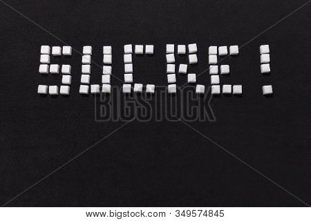 The Word Sugar In Stacked Of Sugar Cubes In French On A Black Background.