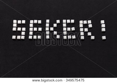 The Word Sugar In Arranged From Cubes Of Sugar In Turkish On A Black Background.