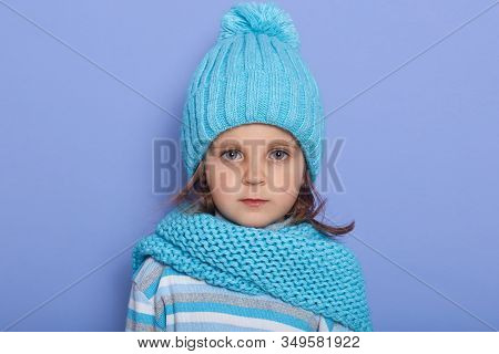 Indoor Shot Of Little Serious Girl Wearing Cap, Scarf And Striped Shirt Standing Isoalted Over Lilac