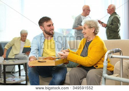 Young Man Serving Dinner For Elderly Woman In Geriatric Hospice. Senior People Care