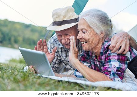 Happy senior couple in tent with tablet computer has fun at video chat