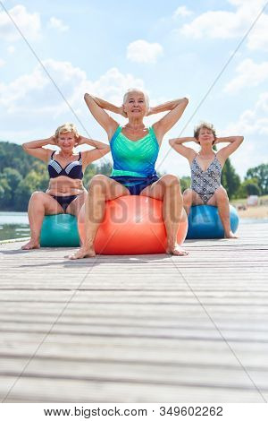 Senior women in a back exercises gymnastics with gym balls in rehab