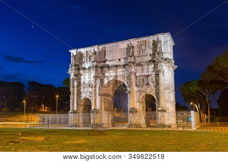 Arch of Constantine illuminated at night in Rome, Italy