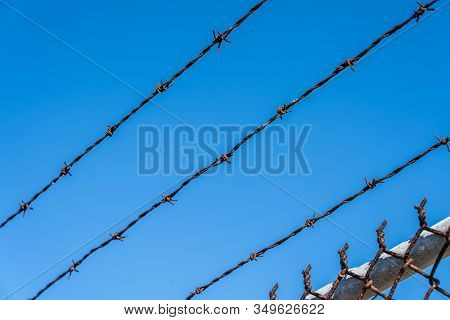 Metal Fence With Barbed Wire On A Blue Sky.