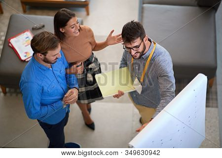 sales manager showing to a young couple options for their home interior design on a panel. showing, explaining, persuasion concept