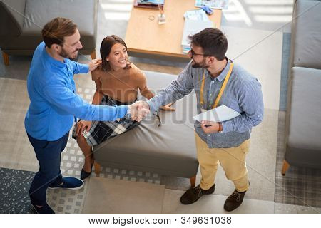 two young confident men shacking hands while handsome woman is watching. business, deal, buying, selling concept