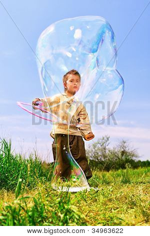 Cute little boy is playing with big bubbles outdoor.