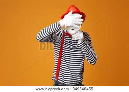 Mime in red hat and in vest with white mask on orange background