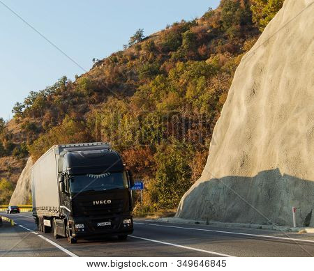 Truck Driving On A Beautiful Mountain Road. Black Truck Trailer Carrying Goods On Highway. Cargo Tra