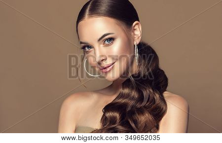 Beautiful Girl . Fashionable And Stylish Woman In Trendy Jewelry Big Earrings .curly Ponytail Hairst