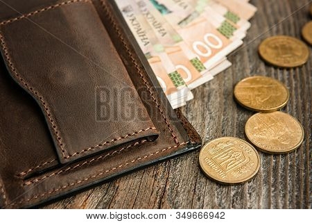 Brown Leather Wallet With Banknotes And Coins On Old Wooden Surface. Close Up.