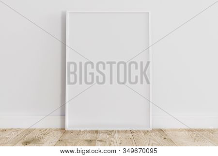 Empty Thin White Frame On Light Wooden Floor With White Wall Behind It. Empty Poster Frame Mockup. E
