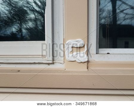 Hole In Damaged Metal Frame Of Window On House Witch Caulk