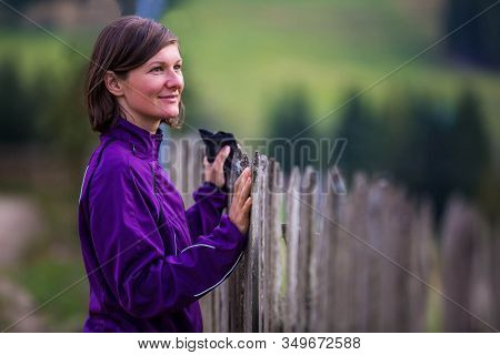 Beautiful Woman In A Purple Coat Standing By The Fence