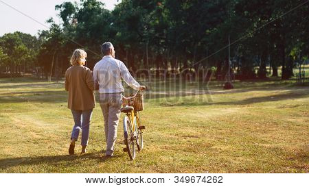 The Behind Of Caucasian Elderly Couples Walking With A Bicycle In The Natural Autumn Sunlight Garden